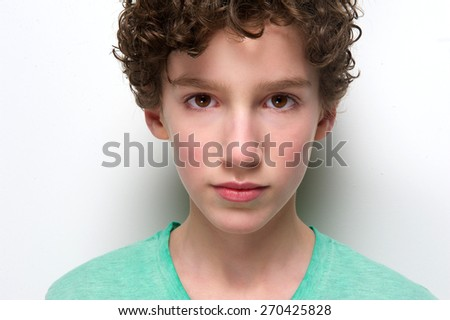 Close up portrait of a boy posing against white background staring  - stock photo