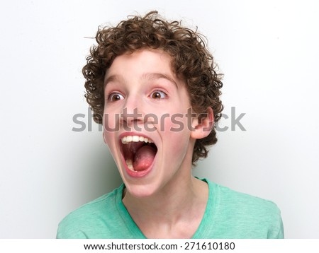 Close up portrait of a boy with mouth open having a surprised expression  - stock photo