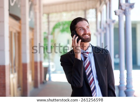 Close up portrait of a businessman smiling and talking on mobile phone in town - stock photo