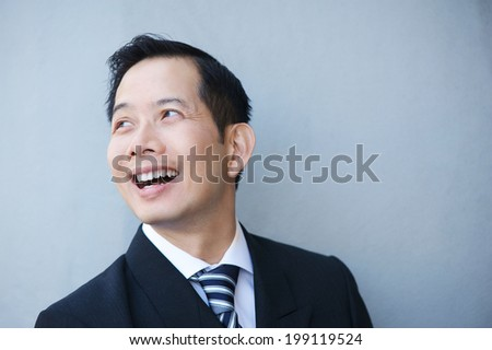Close up portrait of a businessman smiling on gray background - stock photo