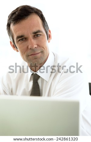 Close up portrait of a businessman using laptop at workplace - stock photo