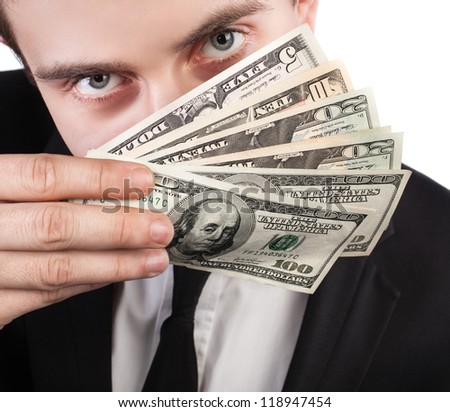 Close-up portrait of a businessman with a fan of dollars covering his face
