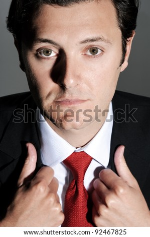 Close up portrait of a businessman with a red tie looking up, holding on to his lapels