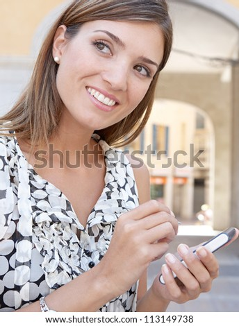 Close up portrait of a businesswoman using a digital tablet while standing next to some arches in the city, smiling.