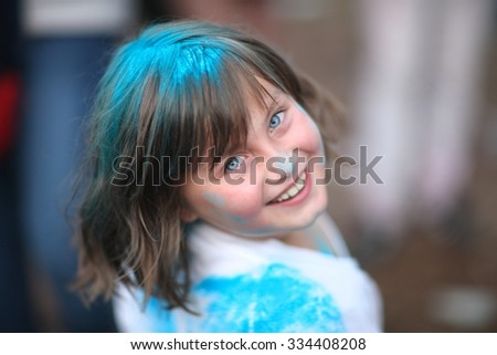 Close-up portrait of a charming girl having fun at holi festival - stock photo