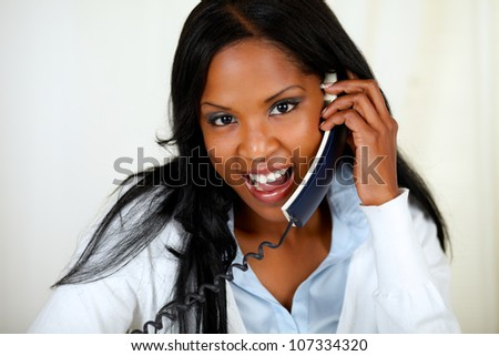 Close up portrait of a charming young woman speaking on phone - stock photo