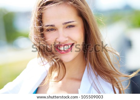 Close-up portrait of a cheerful beauty on a windy day