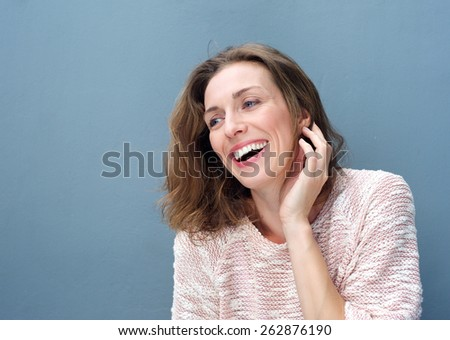 Close up portrait of a cheerful woman laughing with hand in hair - stock photo