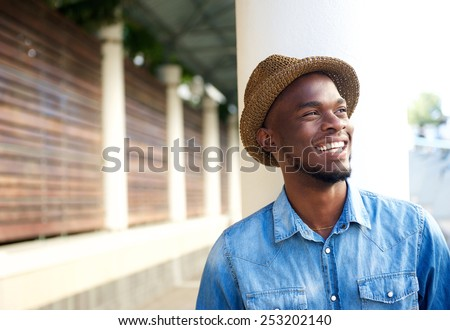Close up portrait of a cheerful young african american man laughing - stock photo