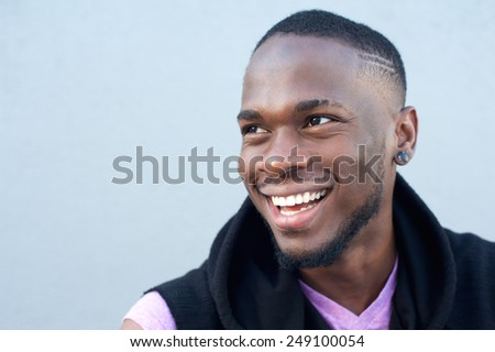 Close up portrait of a cheerful young african american man smiling against gray background  - stock photo