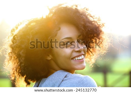 Close up portrait of a cheerful young african american woman smiling outdoors - stock photo