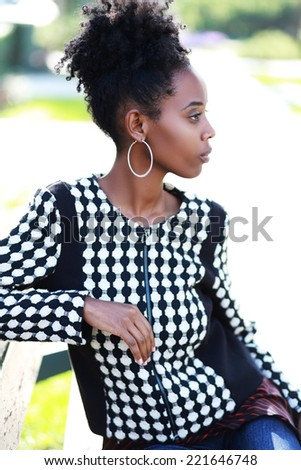 Close up portrait of a cheerful young african woman smiling outdoors - stock photo