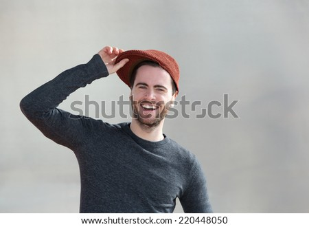 Close up portrait of a cheerful young man laughing with hat