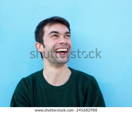 Close up portrait of a cheerful young man smiling against blue background - stock photo