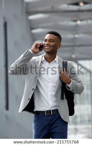 Close up portrait of a cheerful young man talking on mobile phone - stock photo