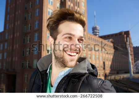 Close up portrait of a cheerful young man walking in the city - stock photo