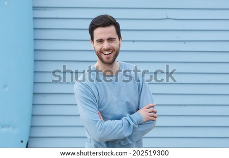 Close up portrait of a cheerful young man with beard smiling with arms crossed - stock photo