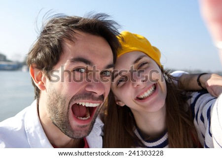 Close up portrait of a cheerful young smiling couple taking selfie