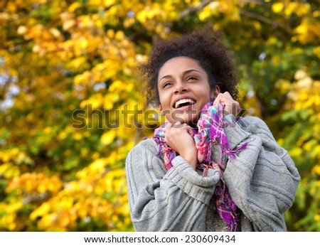 Close up portrait of a cheerful young woman smiling in autumn - stock photo