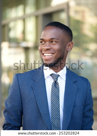 Close up portrait of a confident businessman smiling in the city - stock photo