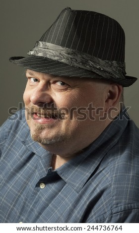 Close up portrait of a confident middle aged man with beard and hat smiling on gray background - stock photo