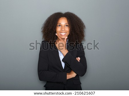 Close up portrait of a confident young business woman thinking on gray background