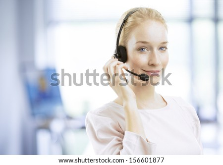 Close-up portrait of a confident young female customer service agent with headset working in office