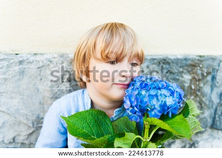 Close up portrait of a cute blond toddler boy playing with a big beautiful flower outdoors - stock photo