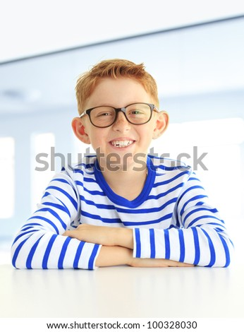 Close up portrait of a cute boy sitting in the school - stock photo