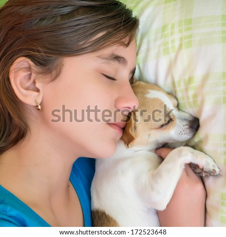 Close-up portrait of a cute girl sleeping with her little chihuahua dog - stock photo