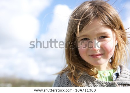 Close up portrait of a cute girl smiling outdoors - stock photo