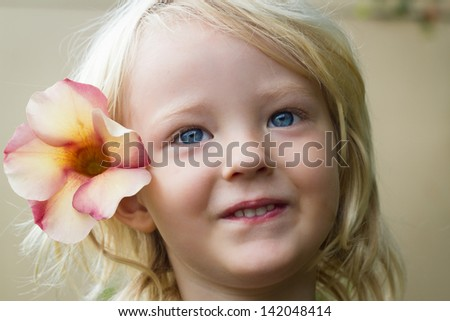 Close-up portrait of a cute, happy child with a flower in their hair.