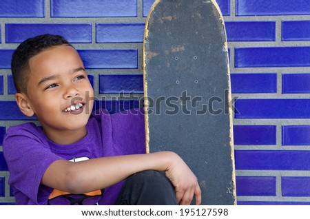 Close up portrait of a cute kid smiling outdoors with skateboard - stock photo