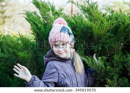 Close up portrait of a cute little girl in winter time with spruce on background waves her hand