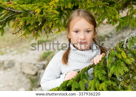 Close up portrait of a cute little girl of 8 years old, wearing warm grey roll neck pullover, having fun outdoors - stock photo