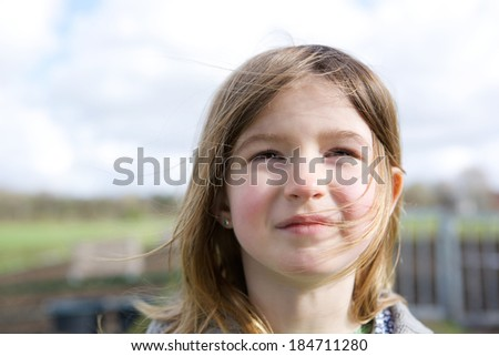Close up portrait of a cute little girl thinking and looking up outdoors - stock photo