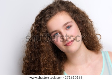 Close up portrait of a cute teenage girl with curly hair smiling on white background - stock photo
