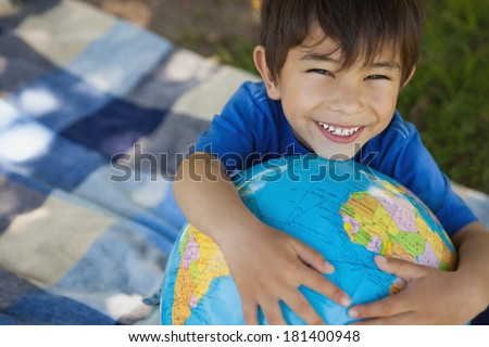 Close-up portrait of a cute young boy holding globe at the park - stock photo