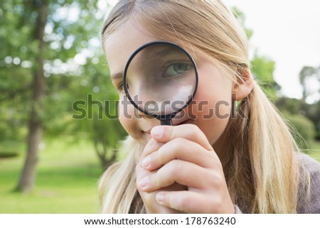 Close-up portrait of a cute young girl looking through magnifying glass at the park - stock photo