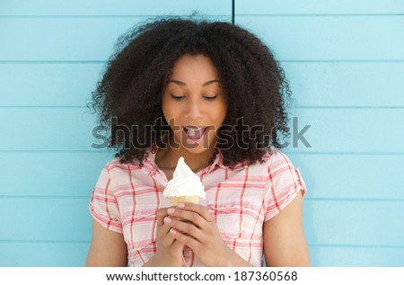 Close up portrait of a cute young woman looking surprised with ice cream outdoors - stock photo