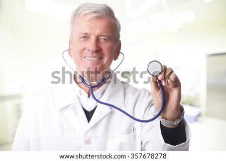 Close-up portrait of a doctor holding a stethoscope up to the camera. The senior male doctor wearing a white medical coat while looking at the camera and smiling.
