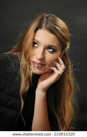 close up portrait of a dreamer girl looking up and leaning her head on her hand isolated on black background - stock photo