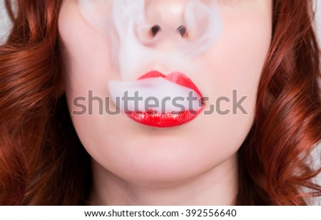 close-up portrait of a elegant young redhead woman, bright red lips, the smoke releases - stock photo