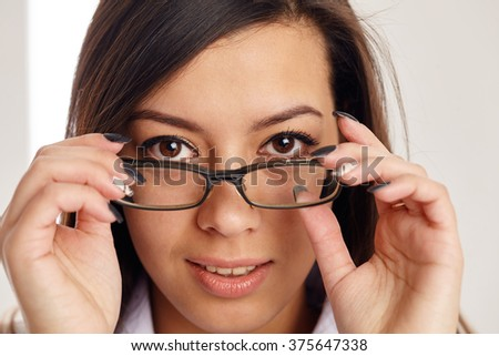 Close up portrait of a face of a young businesswoman, holding glassess. - stock photo