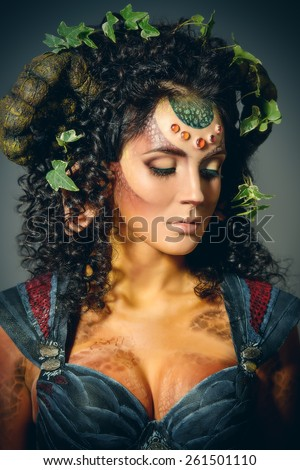 Close-up portrait of a fairy female Faun. Myth and fantasy. Body painting project. Studio shot. - stock photo