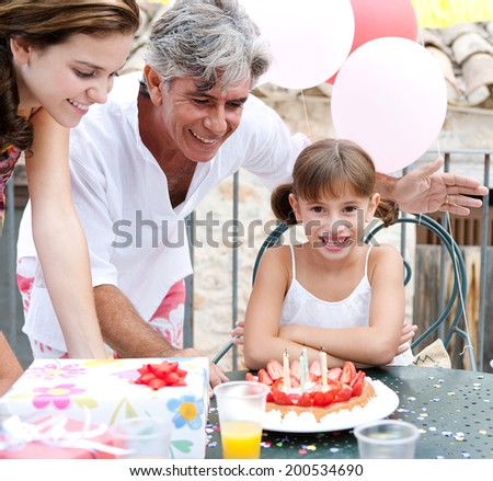 Close up portrait of a family celebrating a young girl birthday outdoors, with a strawberry cake with candles and gifts, confetti and balloons. Family celebrating and fun lifestyle activities. - stock photo