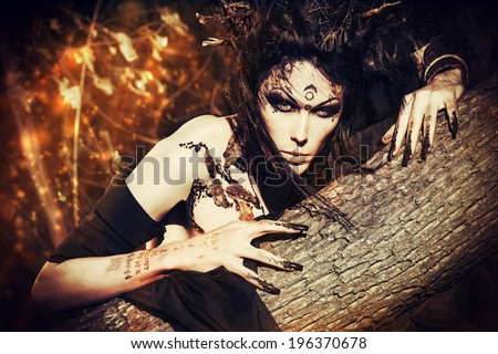Close-up portrait of a fantasy man in a wild wood. Art project. Fantasy. Halloween. - stock photo