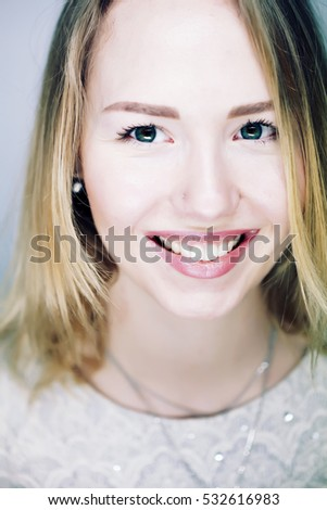 Close-up portrait of a fashion blonde with stylish short hairstyle. Young cute smiling girl with perfect white teeth