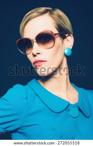 Close up Portrait of a Fashionable Young Woman in Elegant Blue Dress and Sunglasses. Isolated on Dark Blue. - stock photo