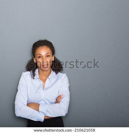 Close up portrait of a female business person with arms crossed on gray background - stock photo